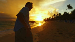 Man running on the beach at sunset stock footage