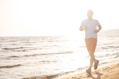Man running on the beach at sunset. Young Man running on the beach at sunset Royalty Free Stock Photo