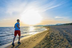 Man running on the beach at sunset. Young Man running on the beach at sunset Royalty Free Stock Image