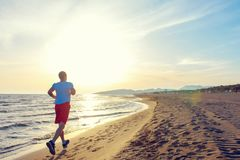 Man running on the beach at sunset. Young Man running on the beach at sunset Stock Image