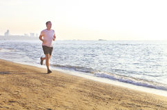 Man running on the beach at surise Royalty Free Stock Photo