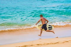 Man running on beach to skimboard Royalty Free Stock Images