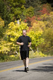 Man running in black. Man running down a black top road in the fall Stock Image