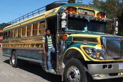 Man on the running board of a bus. SAN JUAN LA LAGUNA, GUATEMALA -  NOVEMBER 27: Close-up of a colored bus in the town center with a man on the running board Stock Photo