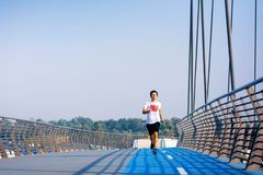 Man running on the bridge on a sunny day stock photography