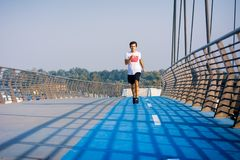 Man running on the bridge on a sunny day stock image
