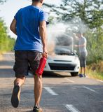 Man running with a car extinguisher to help another driver to extinguish car fire. Man running with a car extinguisher to help another driver to extinguish a car royalty free stock photo