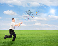 Man running and catching butterflies with net on a field Stock Image
