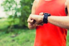 Man running and checking sport smart watch Stock Photo