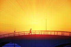 Man running crossing a bridge next to the beack at sunset. Empty copy space for Editor`s text Royalty Free Stock Image