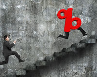 Man running after 3D red percentage sign with human legs Royalty Free Stock Photos