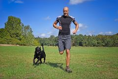 Man running with dog Royalty Free Stock Image