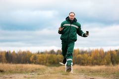 Man running with dogs. Man running with two dogs while training them on autumn lawn stock images