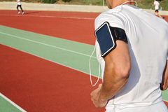 Man running down stadium track. Male runner  listening to music on mp3 player or mobile phone Royalty Free Stock Photo