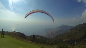 Man running downhill to take off with paraglide over city, marine view at back. Stock footage stock video footage