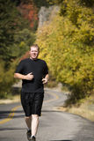 Man running fall colors. Man running down the road in the fall Stock Photo
