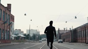 Man running fast in the middle of an old street. Real time shot. Freedom. Camera follows sportsman between tram tracks. Man running fast in the middle of the stock footage
