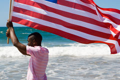 Man running with flag. Young african america man running with a USA flag on beach Royalty Free Stock Photo