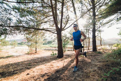 Man running in a forest outdoors Stock Image