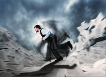 Man running in frustration. Against papers Royalty Free Stock Images