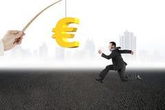 Man running golden euro symbol fishing lure asphalt road citysca Stock Photography