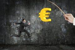 Man running golden euro symbol fishing lure mottled concrete wal Royalty Free Stock Images