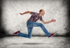 Man running. Gray concrete wall and floor Royalty Free Stock Photo