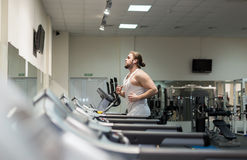 Man running in a gym on treadmill Royalty Free Stock Photo