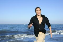Man running happy on the blue summer beach Royalty Free Stock Image