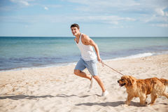 Man running with his dog on the beach royalty free stock images