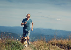Man running with his dog on the mountain tableland Royalty Free Stock Image