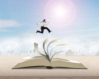 Man running and jumping on open book stock photos