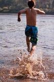 Man running in lake Stock Photos
