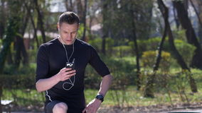 Man running and listening to music and resting for a quick look at social media on smartphone stock video footage