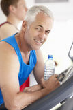Man On Running Machine In Gym Drinking Water Stock Photo