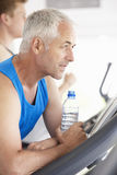 Man On Running Machine In Gym Drinking Water Royalty Free Stock Photos