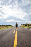 Man running in middle of deserted desert road Royalty Free Stock Photos