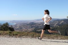 Man running in the mountain with a big city in the background Stock Photography