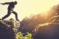 Man running on Mountains jumping cliff over lake. Skyrunning sport Lifestyle Travel concept outdoor Royalty Free Stock Image