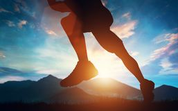 Man running in the mountains at the sunset. Stock Photos