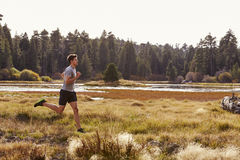 Man running in nature near a lake, side view Royalty Free Stock Photography