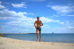Man running out the sea Stock Image
