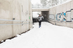 Man running out of subway tunnel in winter Stock Photo