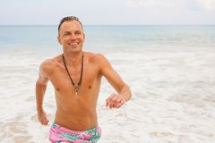Man running out of water in ocean. Handsome man running out of water in ocean Royalty Free Stock Photography