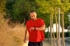 Man running outdoors checking time on watch Stock Photos