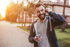 Man running outdoors. Handsome man in earphones is having rest and listening to music during running outdoors near modern private houses stock photography