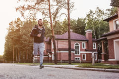 Man running outdoors. Handsome man in earphones is running outdoors near modern private houses stock images