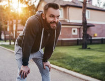 Man running outdoors. Handsome men is having rest during running outdoors near modern private houses royalty free stock image