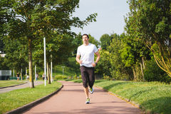 Man running outdoors. Man running on a track in a sunny day Stock Image