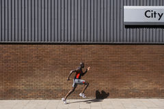 Man Running Past Brick Wall With 'City' Written On It Stock Image